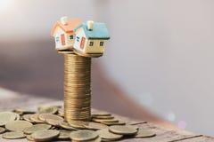 堆的硬币,投资物产、投资风险和不确定性的概念微型房子在不动产房产市场上 库存图片