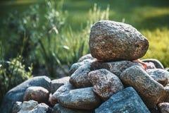 堆石头在一被弄脏的被日光照射了绿叶backgrou的一个庭院里 库存图片