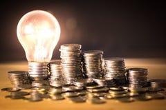 堆硬币和电灯泡保存的金钱概念的,企业规划,成功创造性的想法在将来 库存图片