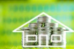 堆硬币当在草的房子形状与绿色bokeh后面 免版税库存图片