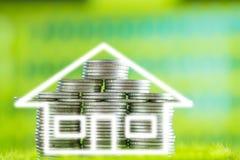 堆硬币当在草的房子形状与绿色bokeh后面 库存照片