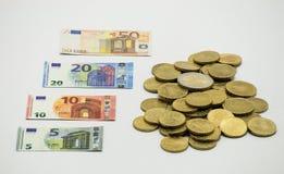 堆硬币,与微型钞票5, 10, 20, 50的欧洲货币欧元欧元 隔绝在与clippin的白色背景 库存图片