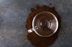 堆碾碎的咖啡,在黑暗的桌上的玻璃杯子顶视图  穿戴女孩褂子早晨白色的咖啡杯 免版税图库摄影