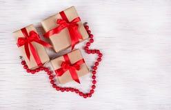 堆礼物盒和红珊瑚项链在白色木背景 节假日概念 复制空间 图库摄影