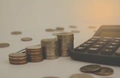 堆积与黑计算器和另一枚硬币的硬币 财务 库存照片
