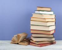 堆积书、精装书五颜六色的书在木桌上和蓝色背景的Open 回到学校 复制文本的空间 库存照片