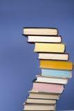 堆积书、精装书五颜六色的书在木桌上和蓝色背景的Open 回到学校 复制文本的空间 库存图片