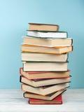 堆积书、精装书五颜六色的书在木桌上和蓝色背景的Open 回到学校 复制文本的空间 图库摄影