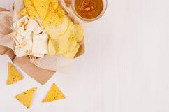 堆积在工艺纸的不同的酥脆金黄快餐,三角烤干酪辣味玉米片,在玻璃的储藏啤酒在软的白色木背景 库存照片