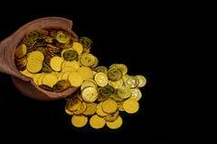 堆积在残破的瓶子的金币在黑背景, 企划投资和保存的未来的金钱堆 图库摄影