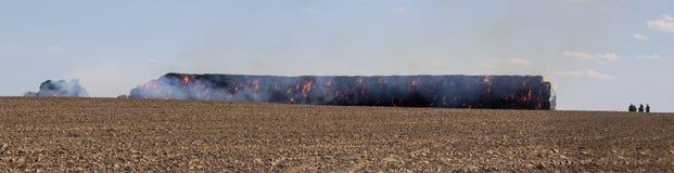 堆积在火的干草的Panoramatic视图在与firemans的领域 库存图片