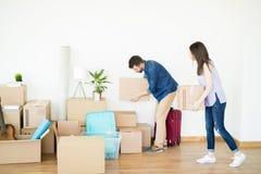堆积在硬木地板上的夫妇纸板箱在新房里 库存图片