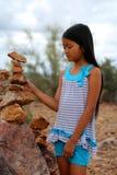 堆积岩石的女孩 免版税库存照片