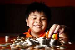 堆积或堆硬币的年轻男孩 免版税图库摄影