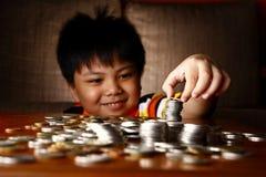 堆积或堆硬币的年轻男孩 库存照片