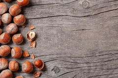 堆积榛树和两枚坚果有残破的壳的在一张老木桌上 复制空间 库存照片
