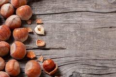 堆积榛树和两枚坚果有残破的壳的在一张老木桌上 库存图片