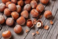 堆积榛树和两枚坚果有残破的壳的在一张老木桌上 免版税图库摄影
