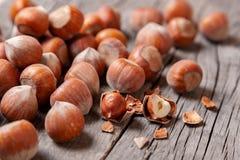 堆积榛树和两枚坚果有残破的壳的在一张老木桌上 库存照片
