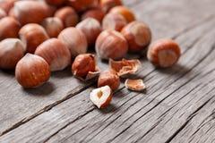 堆积榛树和两枚坚果有残破的壳的在一张老木桌上 免版税库存照片