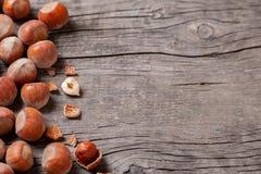 堆积榛树和两枚坚果有残破的壳的在老木桌上 复制文本的空间 库存图片