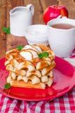 堆积比利时华夫饼干用焦糖调味汁和打好的奶油在板材 库存照片