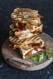 堆积烤烟肉,在木切板的无盐干酪三明治在黑暗的背景,顶视图 可口的早餐 库存照片
