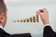 堆积硬币按增长的顺序的商人 图库摄影