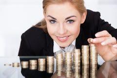 堆积硬币的女实业家 免版税库存图片
