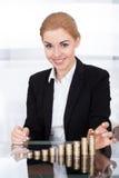 堆积硬币的女实业家 库存图片