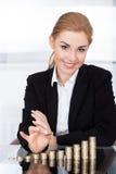 堆积硬币的女实业家 免版税库存照片