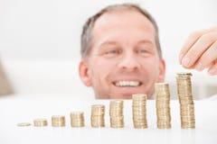 堆积硬币的成熟人 免版税库存图片