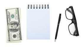 堆积美国金钱一百元钞票、笔记本或者笔记薄,笔,玻璃,隔绝在白色背景裁减路线 免版税库存照片