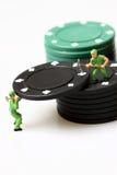 堆积赌博娱乐场芯片的微型工作者 免版税库存图片