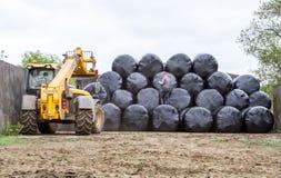 堆积围绕在堆的大包的装载者拖拉机 库存照片