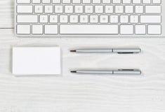 堆空白的名片和笔在白色桌面上 免版税库存图片