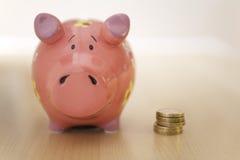 堆站立在存钱罐旁边的金币 免版税图库摄影