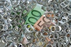 堆箍开罐头用具或延伸圈在金钱钞票作为富有 免版税库存图片
