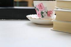 堆精装书书和茶在瓷茶杯的在窗台 免版税图库摄影