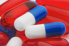 堆红色医疗药片和蓝色青霉素胶囊 库存照片
