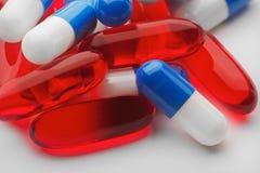 堆红色医疗药片和蓝色青霉素胶囊 免版税图库摄影