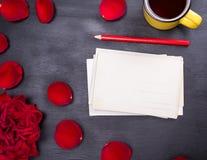 堆纸明信片和一个黄色杯子 免版税库存图片
