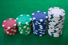 堆纸牌筹码包括红色,白色,绿色和蓝色在绿色背景 透视图 库存照片