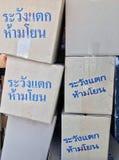 """堆纸箱、灰色颜色和文本的蓝色颜色在""""Warning的泰语的!易碎,不throw† 库存图片"""