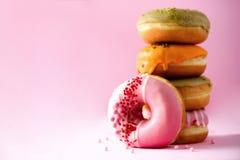 堆给上釉的五颜六色的被分类的油炸圈饼与在桃红色背景洒 复制空间 孩子的甜多福饼 库存照片