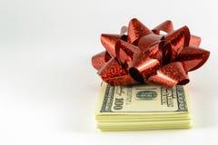堆美元和一件红色礼物鞠躬 免版税库存照片