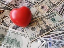 堆美国货币和红色心脏塑造背景 库存图片
