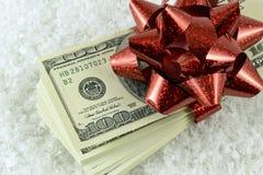 堆美金和一件红色礼物在假雪鞠躬 免版税库存照片