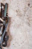 堆老葡萄酒工具包括板钳、扳手、工具、锯条和被分类的零件在混凝土平展放置了 库存图片