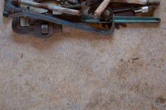 堆老葡萄酒工具包括板钳、扳手、工具、锯条和被分类的零件在混凝土平展放置了 免版税图库摄影